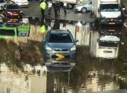 تخليص رجل علق بسيارته بسبب السيول في أحد شوارع حيفا.